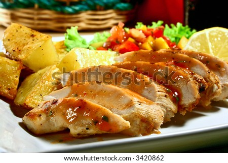 grilled chicken breast with mango salsa and baked potatoes - stock photo