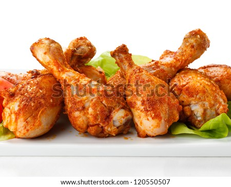 Grilled chicken drumsticks and vegetables on white background - stock photo