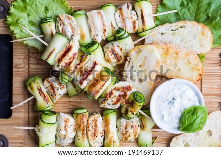 Grilled chicken filet kebab, shashlik on skewers with rolled zucchini, tasty picnic dish - stock photo