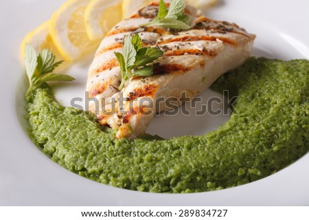 Grilled chicken fillet and mashed mint with green peas close-up on a plate. horizontal