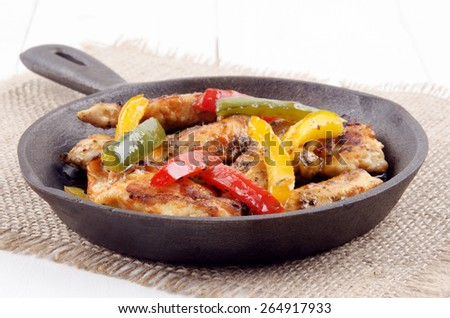 grilled chicken fillet strips with green, red and yellow bell pepper in a cast iron pan on jute - stock photo