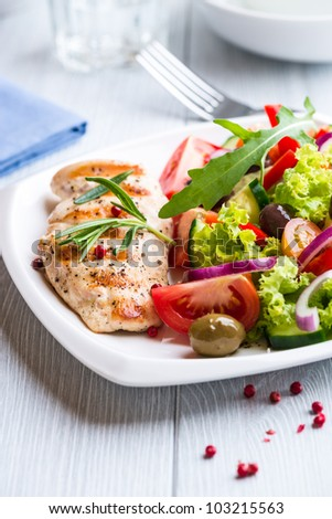 Grilled chicken fillet with mediterranean salad on a plate - stock photo