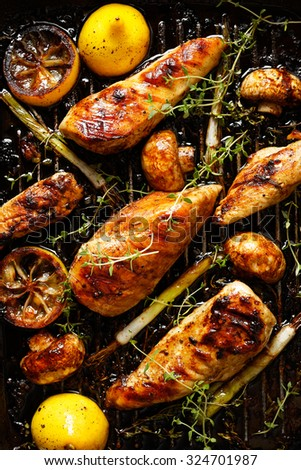 Grilled chicken fillets in the marinade with the addition of mushrooms, green onion, lemon and aromatic herbs on the grill pan - stock photo