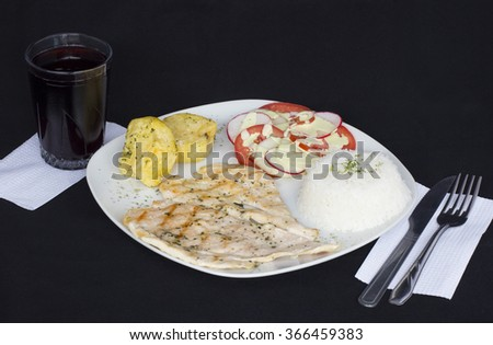 Grilled chicken fillets, potatoes and vegetables, served with a glass of chicha morada (purple corn drink). Peruvian dish. - stock photo