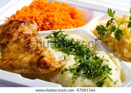 Grilled chicken in styrofoam thermal container with mashed potatoes and carrot salad - stock photo