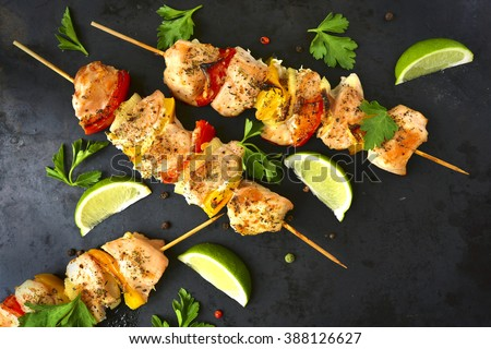 Grilled chicken kebab with vegetables on a black background. - stock photo
