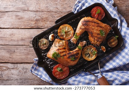 Grilled chicken leg and vegetables on the grill pan. horizontal view from above, rustic style  - stock photo