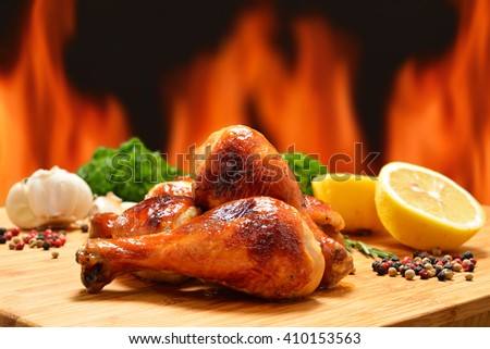 Grilled chicken legs and various vegetables on a chopping wood - stock photo