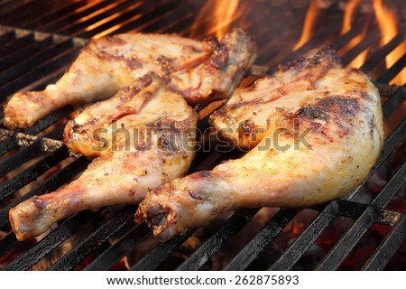 Grilled Chicken Legs On The Hot Flaming Barbecue Grill - stock photo