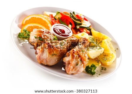 Grilled chicken legs with boiled potatoes and vegetables - stock photo