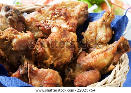 Grilled chicken on a basket with salad on the background - stock photo