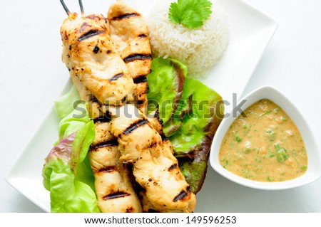 grilled chicken on bamboo skewers with a peanut dipping sauce - stock photo