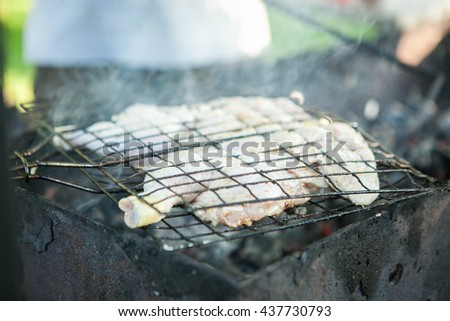 Grilled chicken over flames on a barbecue. - stock photo