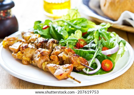 Grilled chicken skewer with rocket salad by bread - stock photo