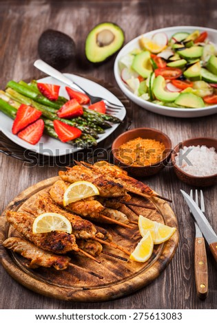 Grilled chicken skewers with green asparagus and avocado salad - stock photo