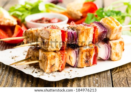 Grilled chicken skewers with vegetables on wooden table - stock photo