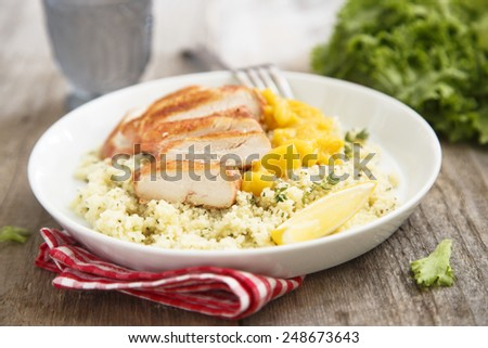 Grilled chicken with couscous and mango - stock photo