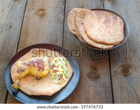 Grilled chicken with naan on wood table - stock photo