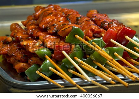 Grilled chiken kebab skewer barbecue meat with pepper and sauce on white dish. - stock photo