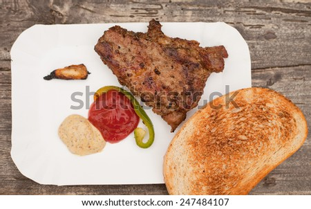Grilled chuck steak on a white plate with grilled roll and sauces. Barbecue in a garden. pork, beef meat. Grilled meat. Food, restaurant, menu. Nobody, macro perspective. - stock photo