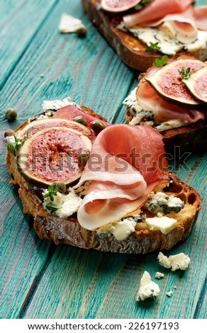 Grilled country bread with ham, blue cheese, fresh figs and capers - stock photo