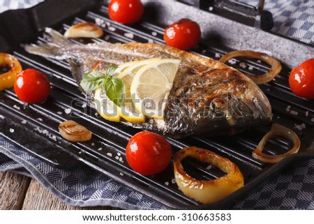 Grilled dorado fish with lemon and vegetables close-up on the grill pan. Horizontal - stock photo