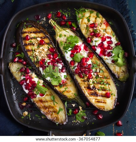 grilled eggplants with garlic yogurt sauce, walnuts and pomegranate, top view, square image - stock photo