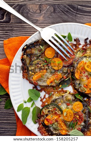 Grilled eggplants with mozzarella, parmesan, tomato, zucchini, capers and herbs - stock photo