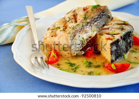 Grilled fish fillet on a white plate - stock photo