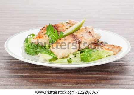 Grilled fish fillet with fresh salad, avocado and colorful spices on white plate isolated on brown background. Culinary healthy seafood eating. - stock photo