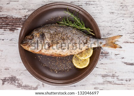 Grilled fish on brown plate with herbs and lemon on white wooden background, top view. Mediterranean luxurious seafood concept. - stock photo