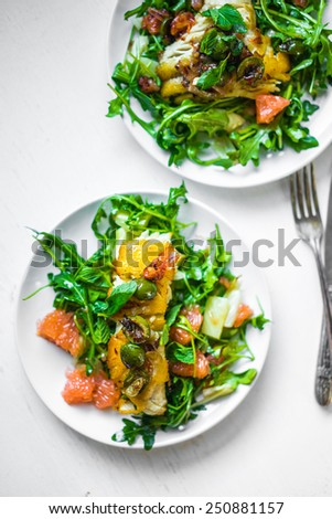 Grilled fish with arugula salad - stock photo