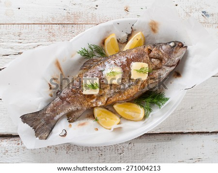 Grilled fish with butter and lemon, selective focus - stock photo