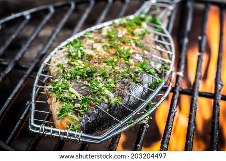 Grilled fish with spices on fire - stock photo