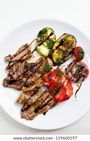Grilled flank beef steak with grilled vegetable on white plate. Overhead shot - stock photo