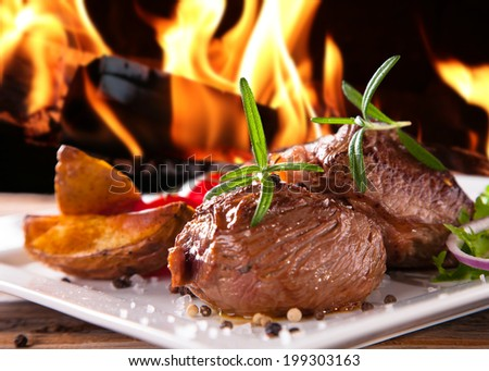 Grilled fresh Beef Steak with flames. Delicious beef steaks with fresh vegetable and trimmings on wooden table.   - stock photo