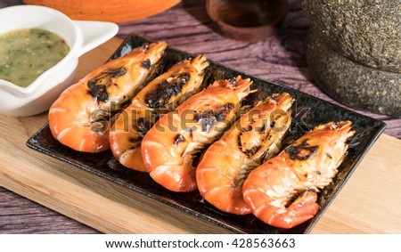 Grilled Giant River shrimp in the dish,Flame grilled large prawns on wood plates, use for seafood, health and wellness related concepts  - stock photo