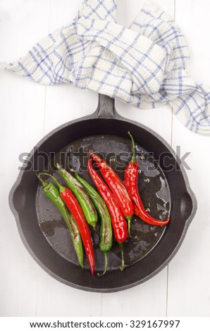 grilled green and red chili in a cast iron pan - stock photo