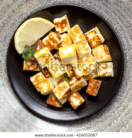 Grilled halloumi cheese cubes with lemon and herbs.  On black plate, top view. - stock photo
