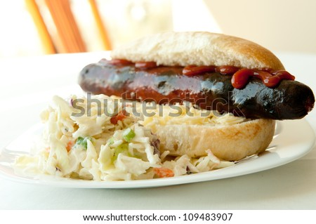 grilled hotdog on a white bun with a side of creamy cole slaw - stock photo
