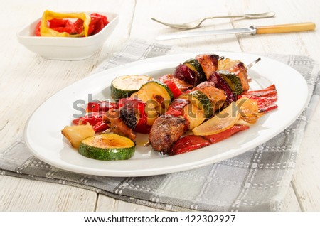 grilled hungarian pork, red pepper, onion and courgette skewers on an white oval plate - stock photo