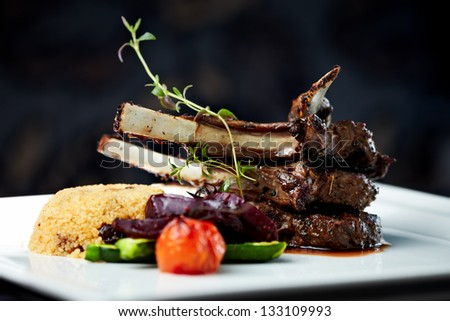 Grilled lamb carre with warm couscous salad, roasted vegetables, Dijon mustard and red wine sauce - stock photo