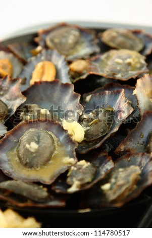 Grilled limpets with lemon. Madeira's traditional dish. - stock photo