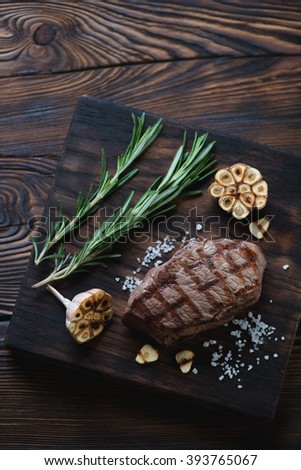 Grilled marbled beef asado steak, rustic wooden setting, high angle view - stock photo