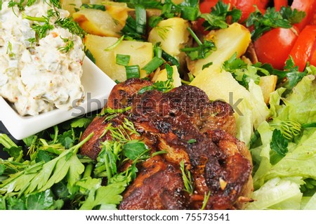 Grilled meat and potatoes. Decorated with tomatoes, lettuce and herbs. - stock photo