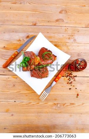 grilled meat beef steaks strips on white plate with pepper and cutlery over wood table - stock photo