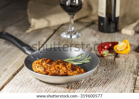 Grilled meat. Frying pan. Vegetables on a wooden table. Rustic style.  Wine in a glass and a bottle of wine.  - stock photo