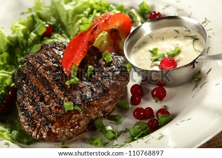 grilled meat in white dish with souce - stock photo