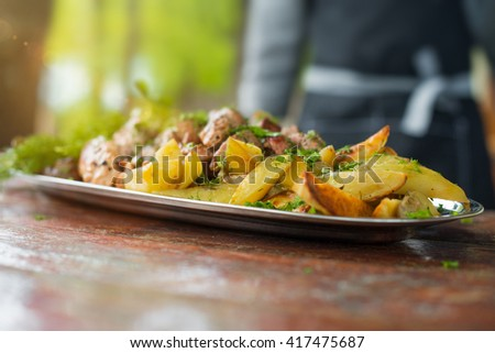 Grilled meat, mushrooms and vegetables (paprika, potatoes, zucchini) served on big plate with herbs - stock photo