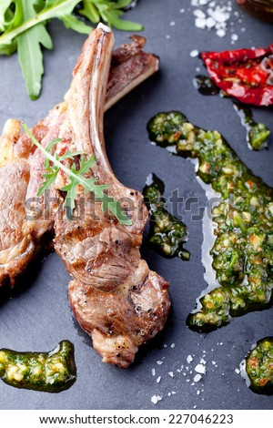 Grilled meat, mutton, lamb rack with fresh salad and sauce on black stone plate.  - stock photo